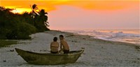 Young Couple watching sunset in Fishing Boat on Palomino Beach Santa Marta Colombia